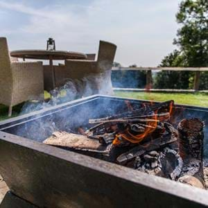 Get cosy round the open firepit at The Clubhouse bar, Treehouse Hotel in Kent