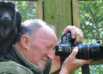 Dave Rolfe, resident photographer at Port Lympne Hotel & Reserve in Kent with a howler monkey